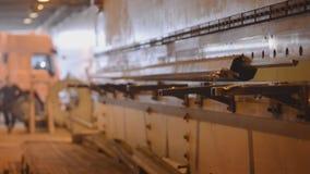 Arbetaren tar bort produkten från den stora maskinen stock video