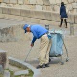 Arbetaren tar omsorg av avskrädemannen Royaltyfria Bilder