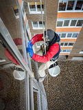 Arbetaren tvättar fönster Arkivbild