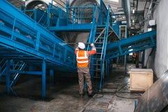 Arbetaren tvättar utrustningen på växten för förlorad sortering fotografering för bildbyråer