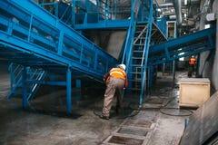 Arbetaren tvättar utrustningen på växten för förlorad sortering arkivbilder