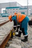 Arbetaren upprättar stålar för lyftande stång arkivbild