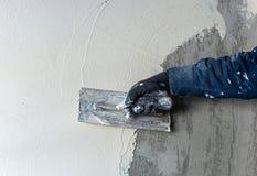 Arbetaren utför inre murbruk Arkivbild