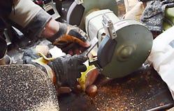 Arbetaren vässar hjälpmedlet på ett malande hjul lager videofilmer
