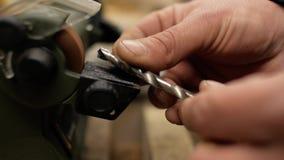 Arbetaren vässar upp drillborren på slut för mala maskin 4K arkivfilmer