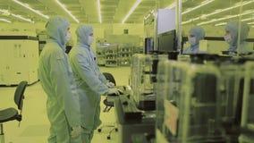 Arbetarforskare för två tekniker i sterilt rent område för maskeringsoveraller Tekniskt avancerad dator som tillverkar nano tekno lager videofilmer