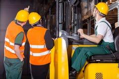 Arbetarfungerande gaffeltruck i lager Arkivfoto