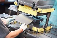 Arbetarfungeringsen belägger med metall täcker pressen bearbetar med maskin Fotografering för Bildbyråer