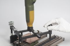 Arbetarhänder på att inrista apparatpantographen med CNC-gravören med boktryckalfabet arkivfoto