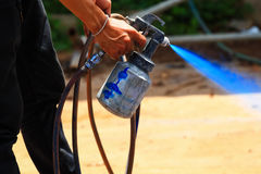 Arbetarhand som målar en blått på utomhus- Arkivbild