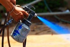 Arbetarhand som målar en blått på utomhus- Royaltyfri Foto
