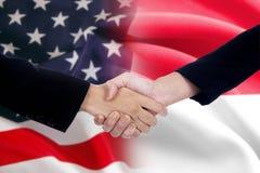 Arbetarhandskakning med amerikan- och indonesflaggorna arkivbild