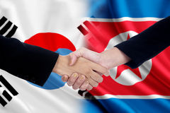Arbetarhandskakning med två koreanska flaggor Royaltyfria Foton