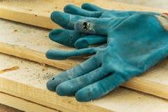 Arbetarhandskar på ett wood snickeribräde arkivbilder