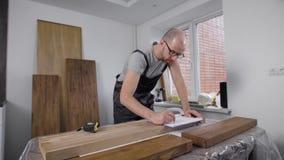 Arbetarhandstil på papper på träbräde med att mäta bandet nära stock video