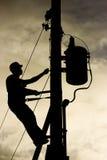 Arbetarkontur på en kraftledningstolpe arkivbild