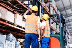 Arbetarlag som tar i logistiklager Arkivfoto