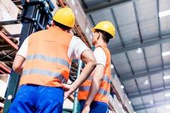 Arbetarlag som tar inventarium i logistiklager Arkivfoto