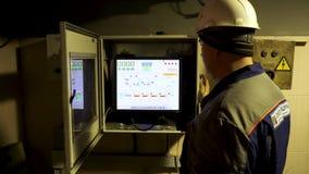 Arbetarman i hemlet och skyddande likformig som kontrollerar data på den industriella datoren, metallurgibegrepp Materiell?ngd i  arkivfilmer