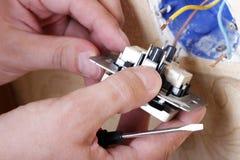 Arbetarmanelektrikeren reparerar skadade håligheter i lägenheten, installation av den nya closeupen arkivfoton