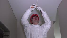 Arbetarmannen klättrar upp på stege och förbereder kabeltrådar för ljus anslutning lager videofilmer