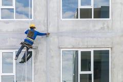 Arbetarmannen som abseiling med repet på konstruktionsplats Arkivbilder