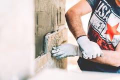 Arbetarmurare som bygger ett hus och en stenläggning med stenen royaltyfria foton