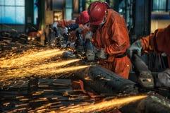 Arbetarna i stålet maler polerar stålet royaltyfria bilder