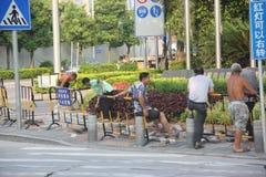 Arbetarna lägger vägar i shenzhen Arkivfoton