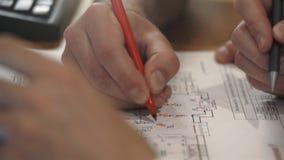 Arbetarna planerar konstruktionen av elektricitet i huset på papper arkivfilmer