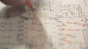 Arbetarna planerar konstruktionen av elektricitet i huset på papper stock video