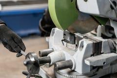 Arbetarsnitt per stycke av material med en cirkelsågmaskin Industriell tekniker som arbetar på att klippa en metall och ett stål fotografering för bildbyråer