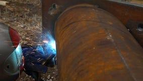 Arbetarsvetsning i en fabrik Svetsning på en industrianläggning stock video