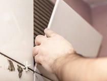 Arbetartileren sätter keramiska tegelplattor arkivbilder