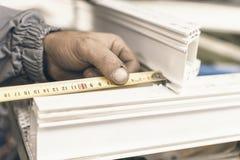 Arbetartillverkningfönster Sårade händer från den manuella arbete och metern Plast- fönster- och dörrbranschproduktion arkivfoton
