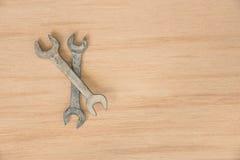 Arbete bearbetar skruvnyckeln, skiftnyckel på en trätabell Royaltyfri Bild
