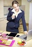 Arbete för affärskvinna, medan ha frukosten hemma med teknologi Arkivfoto