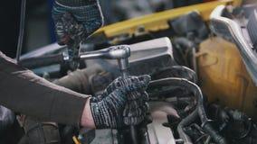 Arbete för bilautomatiskservice - mekanikern skruva av detaljen av bilen royaltyfri bild