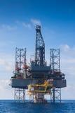 Arbete för fossila bränslenborranderigg över den avlägsna wellheadplattformen till brunnen för avslutningsfossila bränslenjordbru royaltyfri fotografi