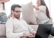 Arbete för modern man på en bärbar dator på hans hem royaltyfri bild