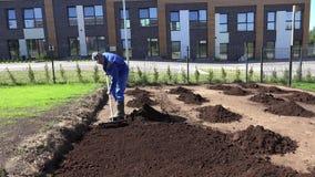 Arbete för radhusägaremannen i gård med krattar hjälpmedlet Jämn fertil jord Statisk elektricitetskott lager videofilmer