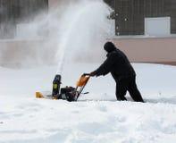 Snowborttagning med en snowblower Arkivfoton