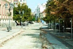Arbete för stadsgatautgrävning på renovering och skadestånd med konstruktionsmaskineri i bakgrunden Arkivbild