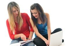 Arbete för två ung flicka på den isolerade bärbar dator Fotografering för Bildbyråer