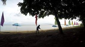 Arbete för ung kvinna som ett strandrengöringsmedel som krattar kullar, skräp på den tropiska sandiga stranden arkivfilmer