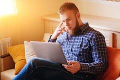 Arbete för ung man som hemma absorberas på bärbara datorn Arkivfoto