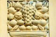 Arbete för väggkonststuckaturen av frukter i korg planlägger på yttersidor av årig tempel 200 arkivfoton