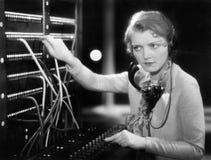 Arbete för ung kvinna som en telefonist (alla visade personer inte är längre uppehälle, och inget gods finns Leverantörgarantier Arkivbild