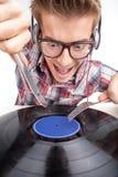 Arbete för ung man som dj med öra-telefoner och exponeringsglas Arkivbilder