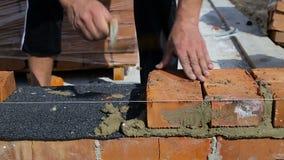 Arbete lägger tegelstenar på en konstruktionsplats på öppen luft lager videofilmer